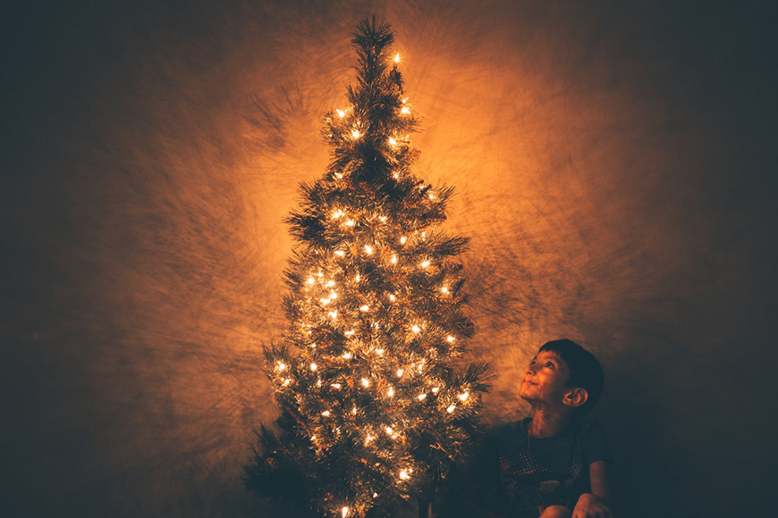 A tree little up with lights and a little boy sitting beside