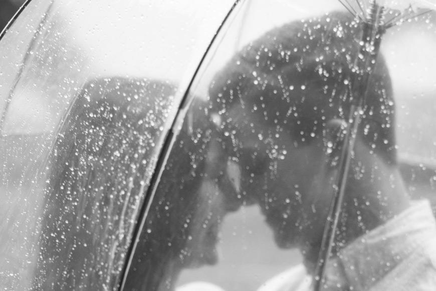 It's raining on a couple under an umbrella
