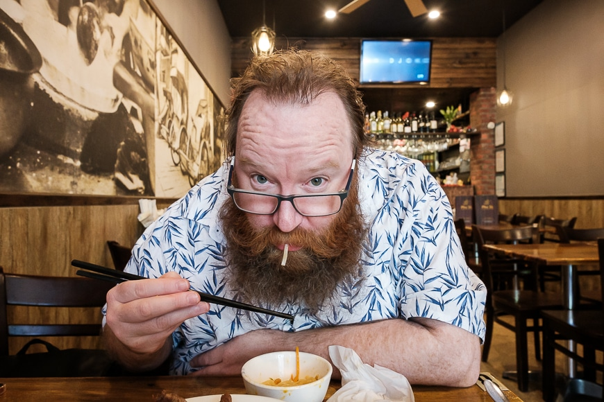 Close up of man with beard eating noodles