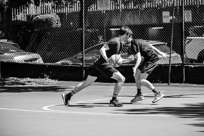 Black and white photo of two men playing basketball