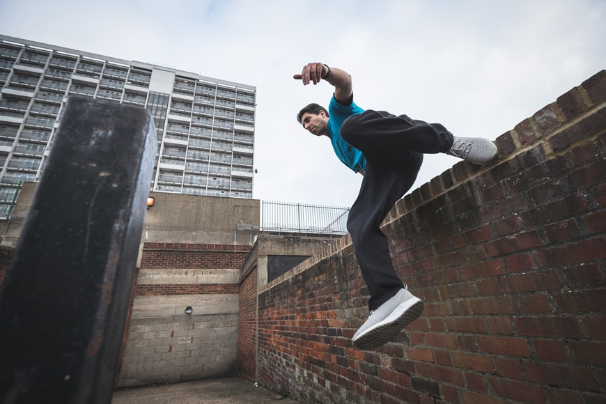 Informal balance - man jumping over a brick wall with a pole in the foreground