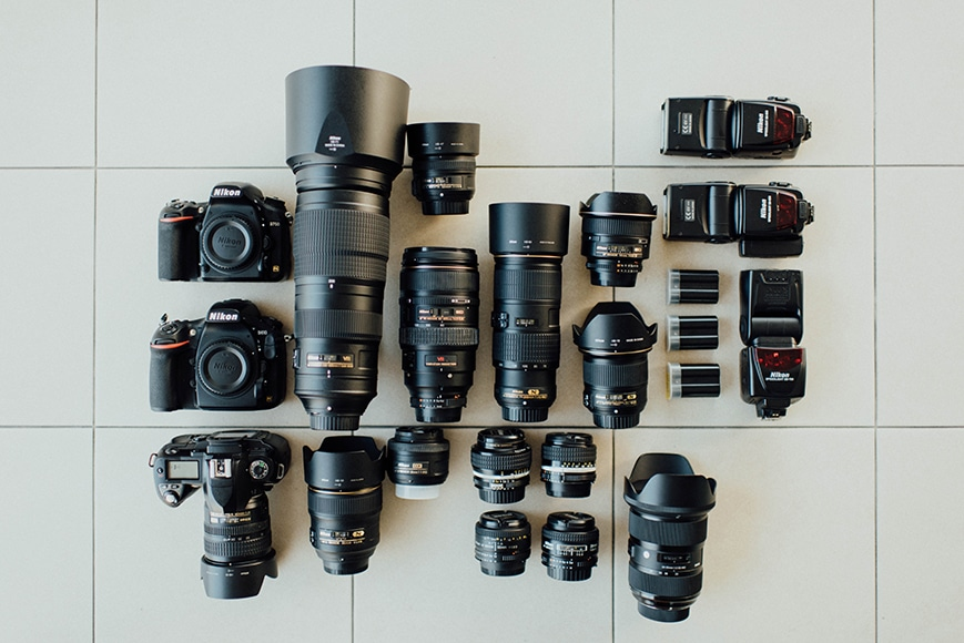 A flat lay featuring a variety of cameras and lenses