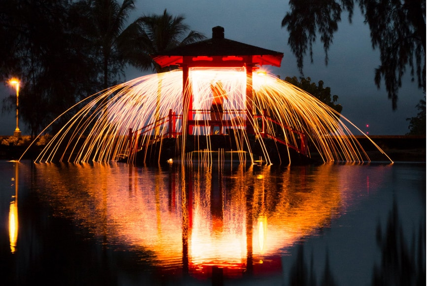 A person standing on a gazebo at night