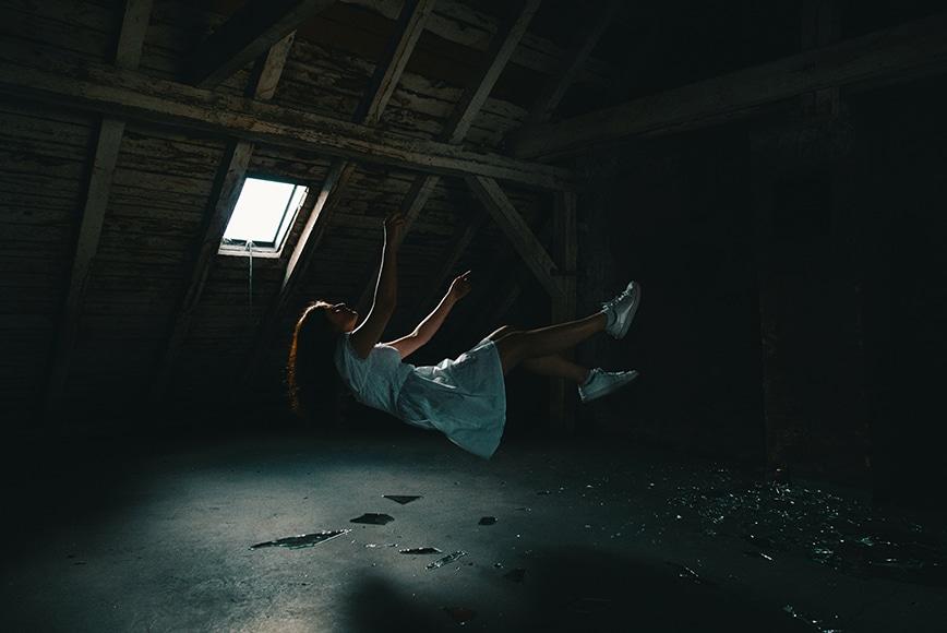 Girl levitating in attic
