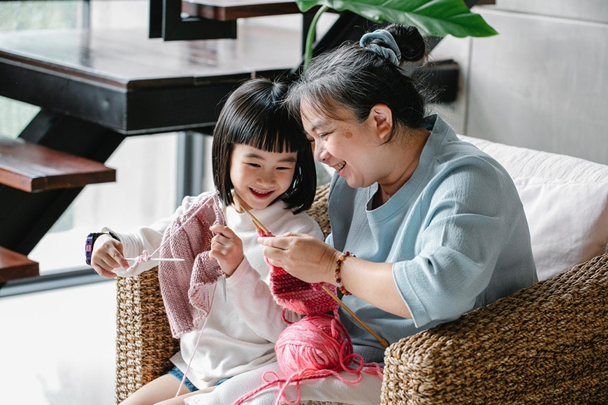 Lifestyle family shot of knitting together with child