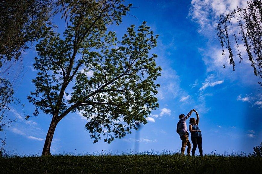 Couple dancing against blue sky