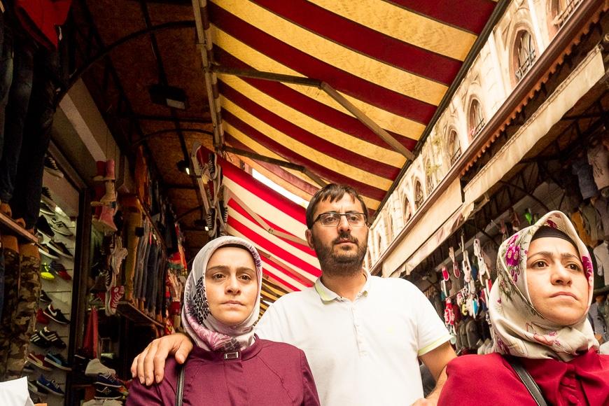 Three people walking through market