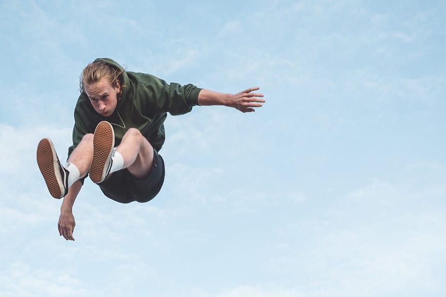 image of a man jumping against a blue sky background