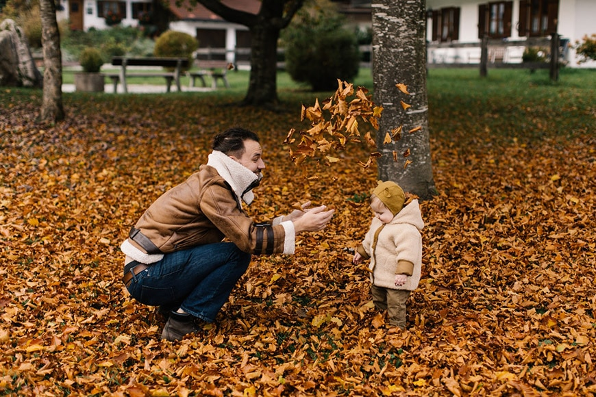 Family portrait photo of a father throwing leaves at child