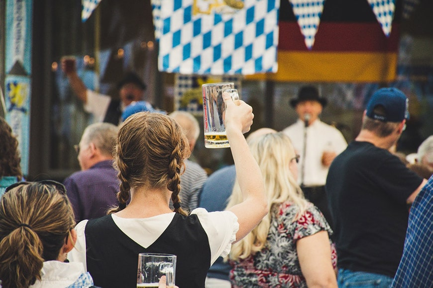 Girl with braids at Oktoberfest holding a beer stein