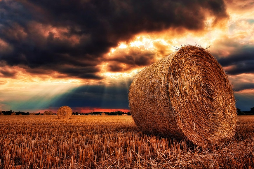Landscape shot of a bale of hay against dramatic clouds