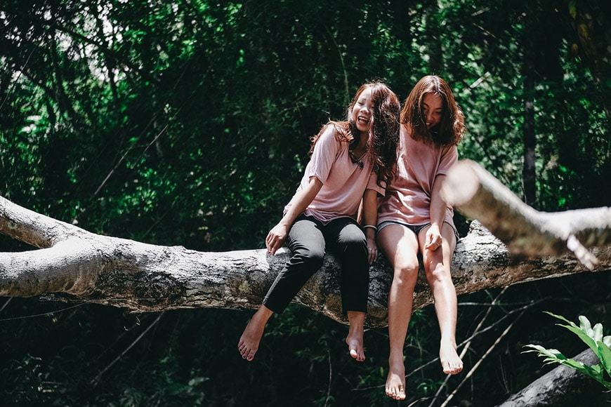 Two girls laughing sitting on tree branch