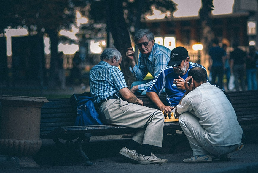 Low light photography of older men playing chess in the park