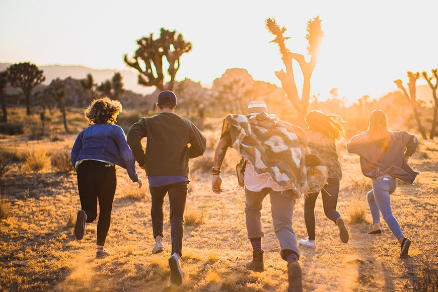 Group of people running through the desert