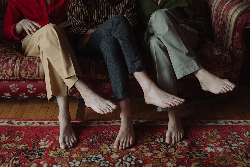 Faceless portrait of three people's legs and feet