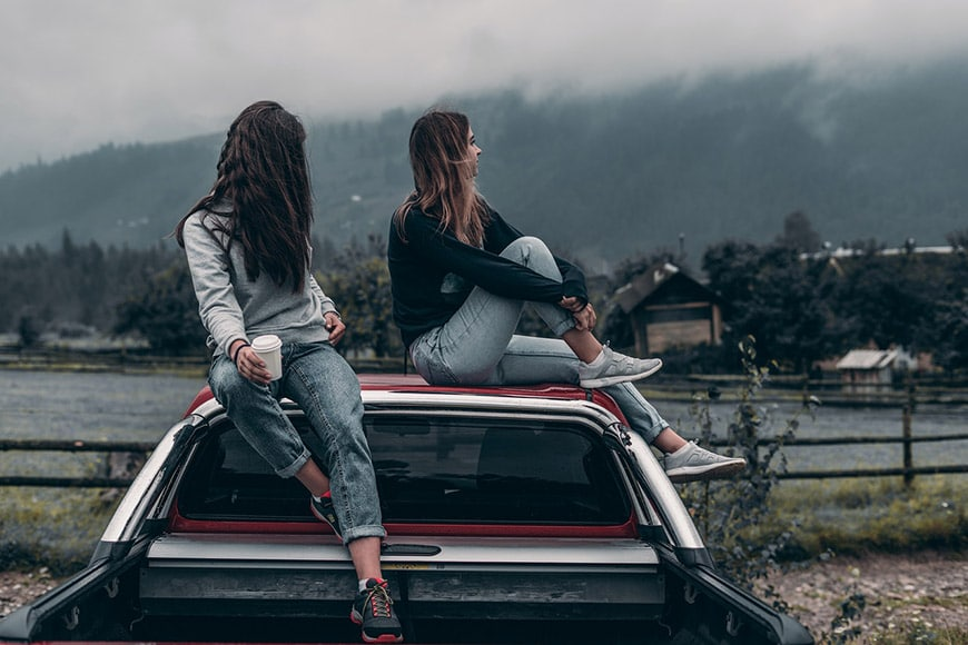Two girls sitting on top of a car