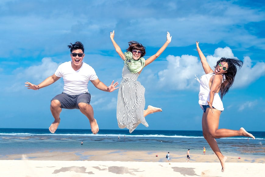 Three friends jumping in the air at the beach