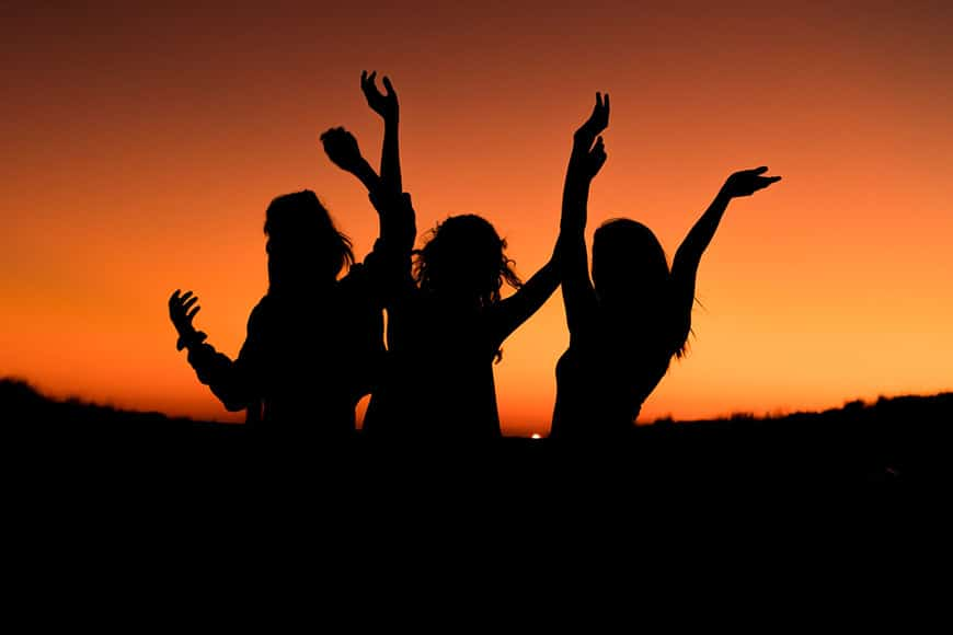 Silhouette of three women with arms in the air