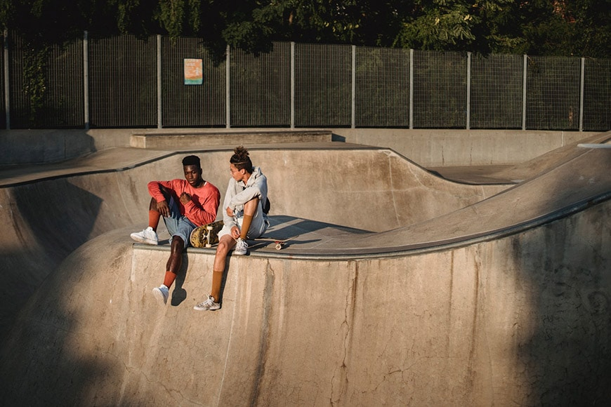 Two guys sitting in a skate park