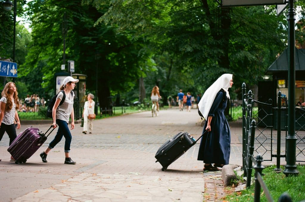 Urban photography - people with suitcases walking through a park