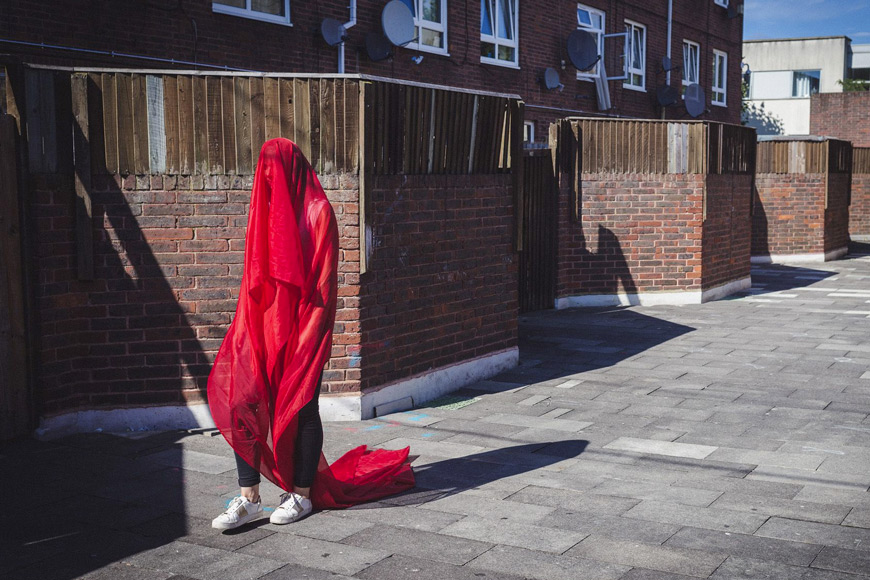 Image of person draped in red fabric walking in urban setting
