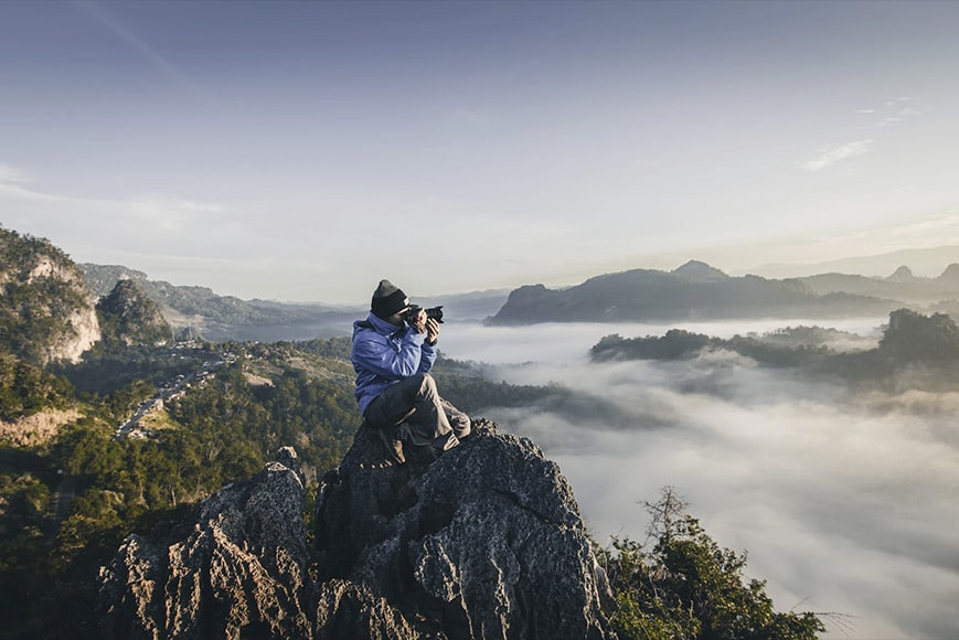 Photographer sitting on rocky outcrop