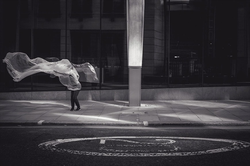 Composition in black and white of person and wind-blown plastic sheet