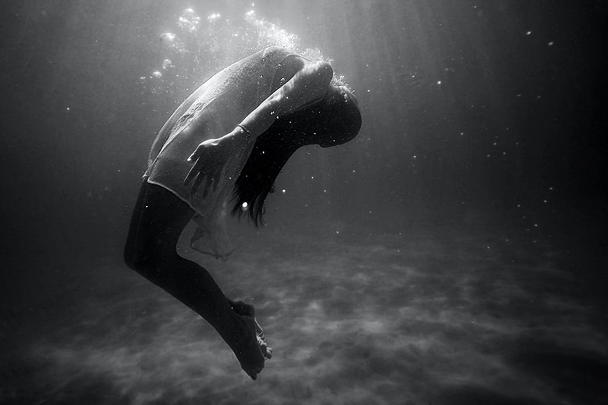 Black and white photo of a women underwater bending backwards