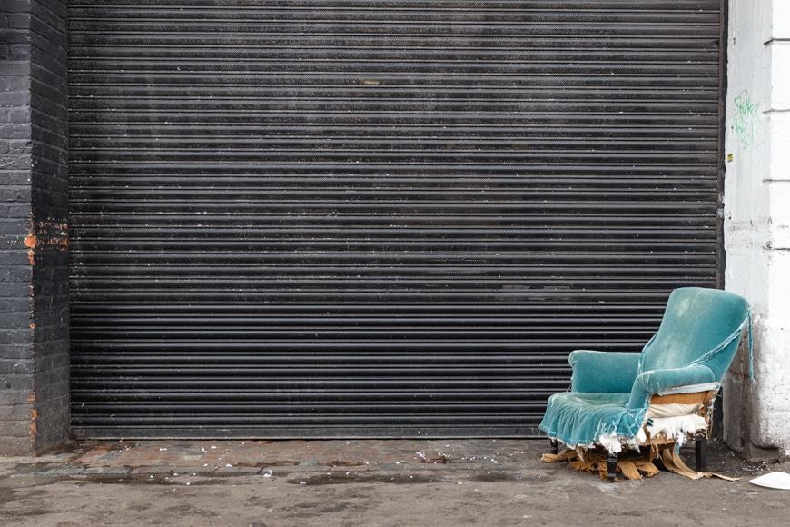 Urban photography - broken velvet armchair in front of garage door