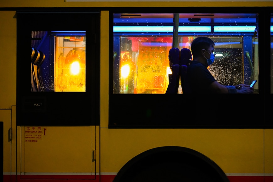 Urban photography - man on a bus wearing a mask at night