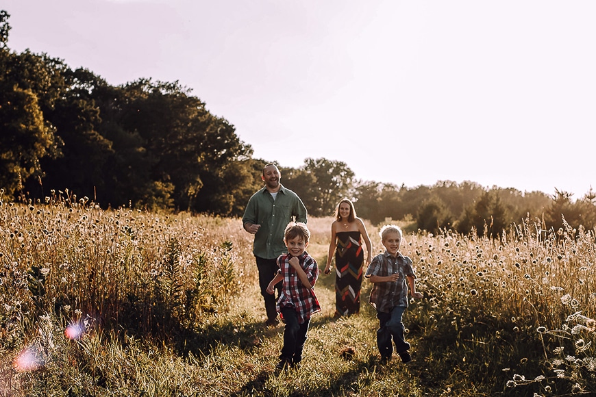 Parents with their two boys walking through a field