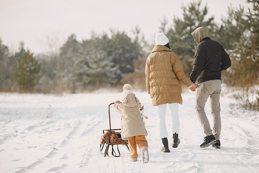 Parents holding hands and walking in the snow with their toddler walking behind