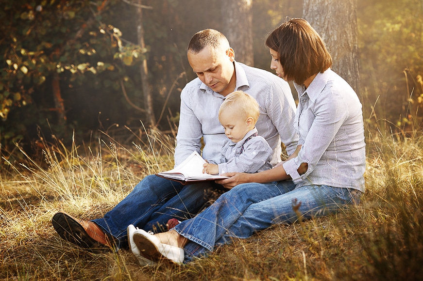 Parents sitting and reading with their one year old in a bush setting