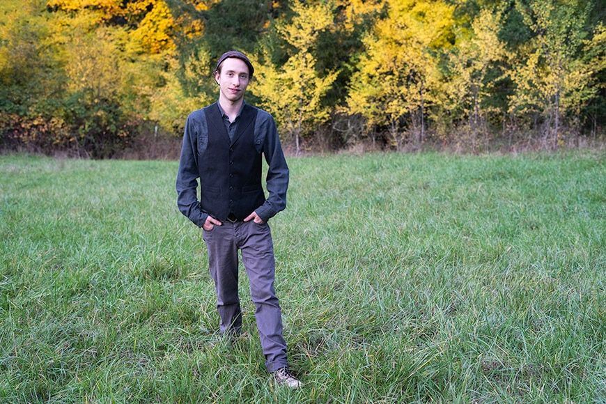Man standing in a grassy field with hands in his pocket