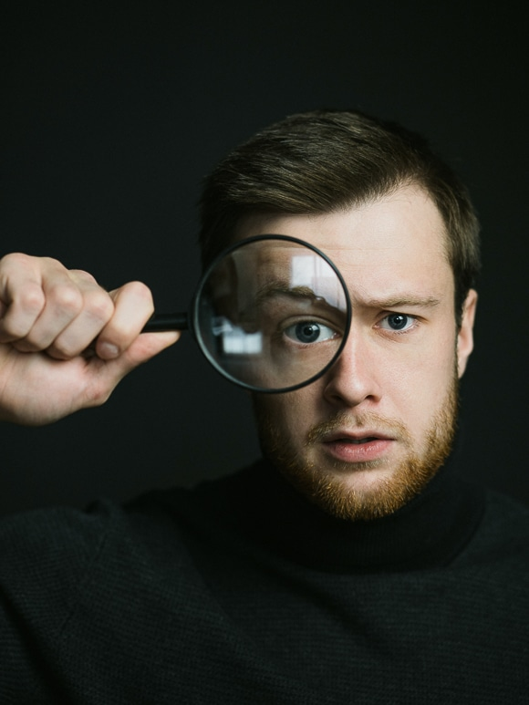 Photoshoot ideas - self portrait of a man with a beard and magnifying glass