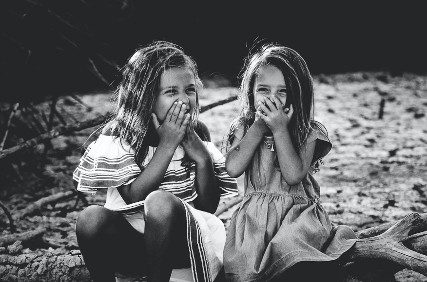 Photoshoot ideas- two young girls sitting and laughing in black and white