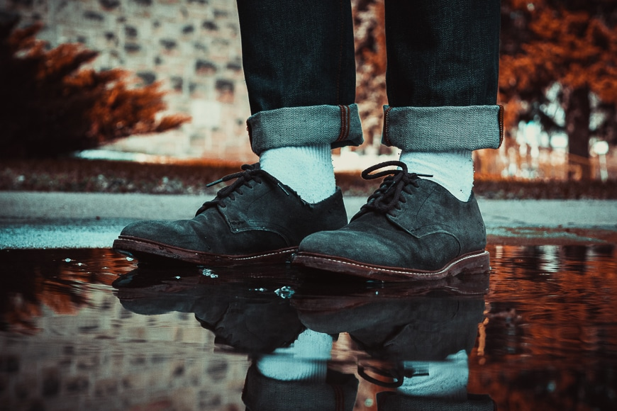 Close up of a persons suede shoes standing in a puddle