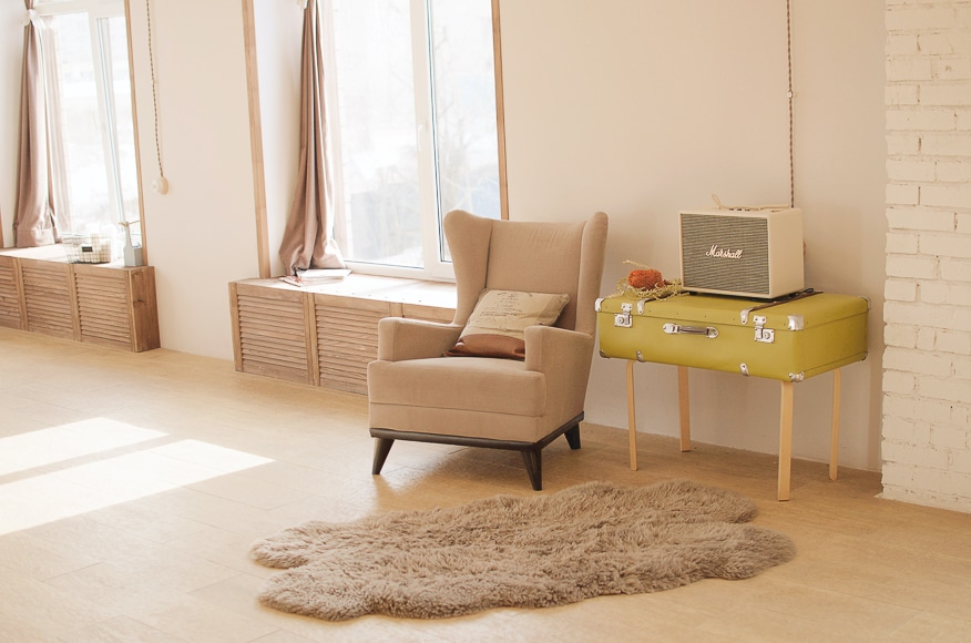 Beige lounge room with one chair and rug