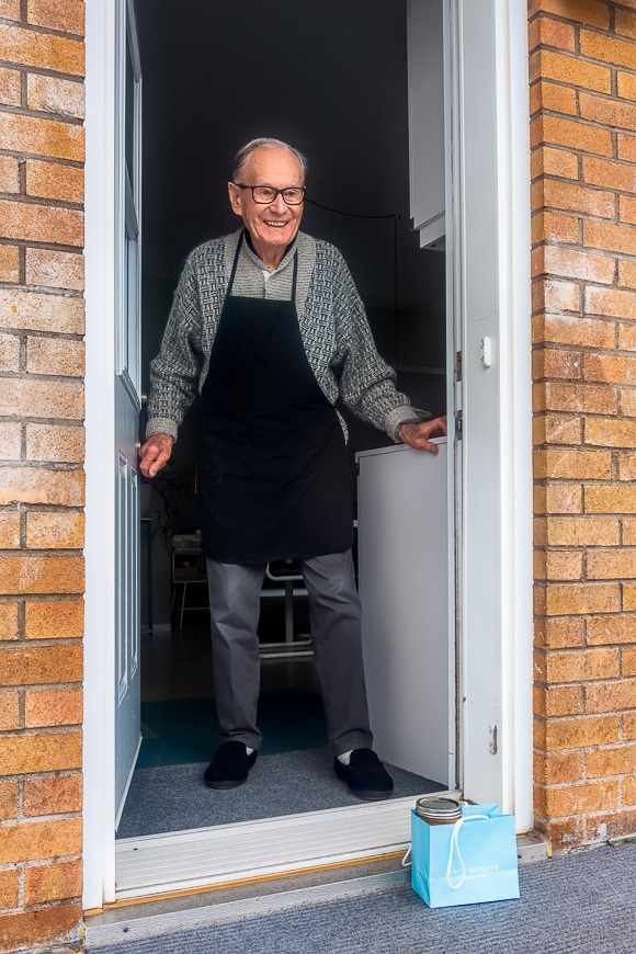Smiling elderly man opening the door to a parcel on the ground