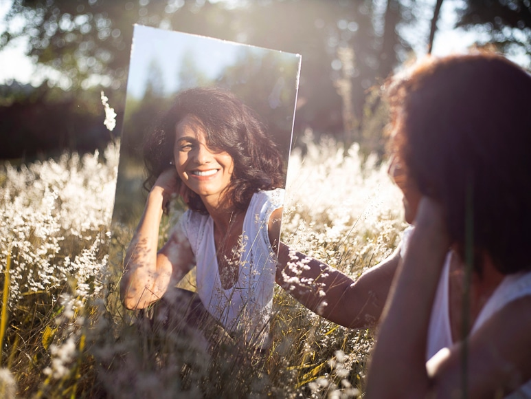 Womens reflection in a mirror sitting in a field of flowers