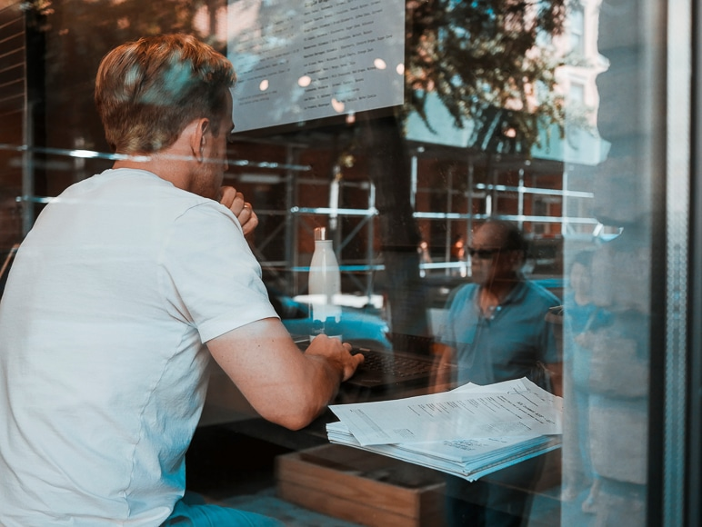 Man sitting in a cafe working with a reflection of people outside on the window