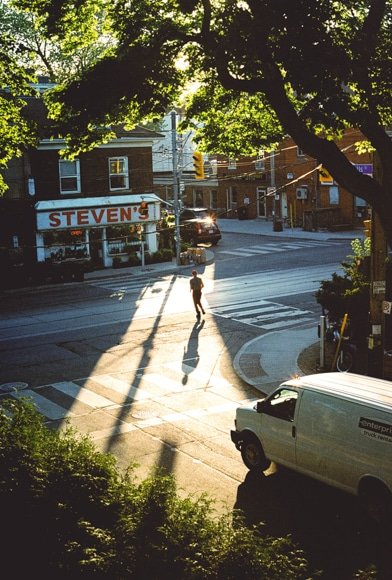 Urban photography - man running across the road towards a shop