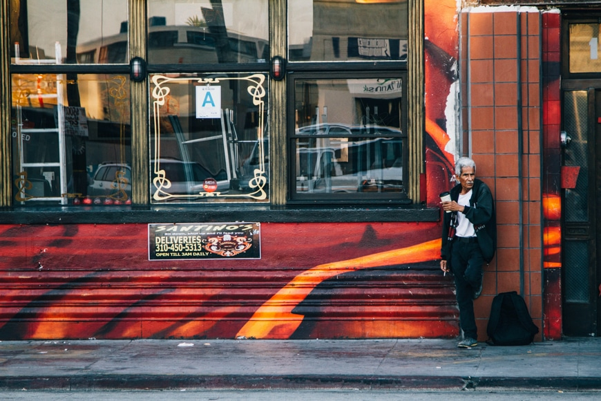 Photography in city - elderly man leaning against a shop front with a coffee