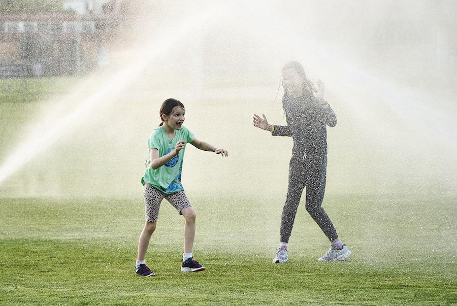 Kids playing in sprinklers