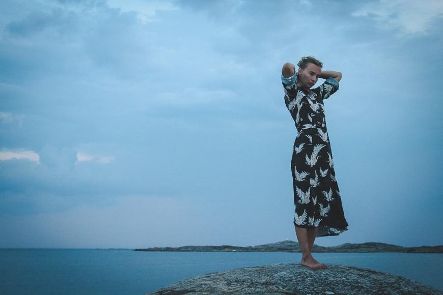 Girl against blue sky standing on rocks