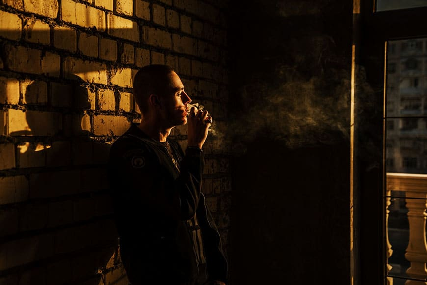 Photo of a man smoking in moody light
