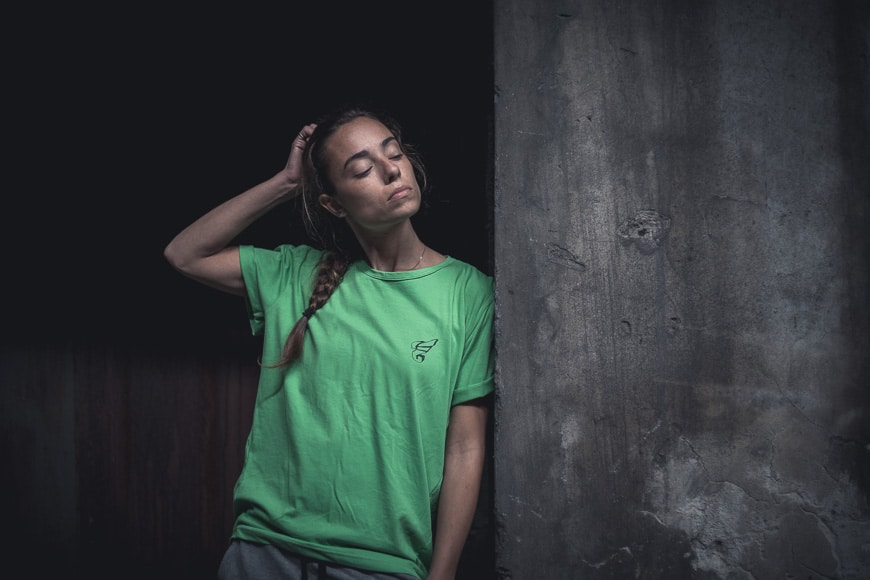 Girl in green standing in shadows