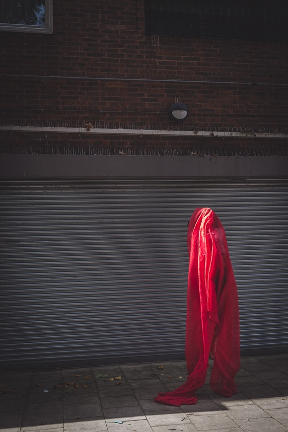 Conceptual photo of person veiled in red fabric