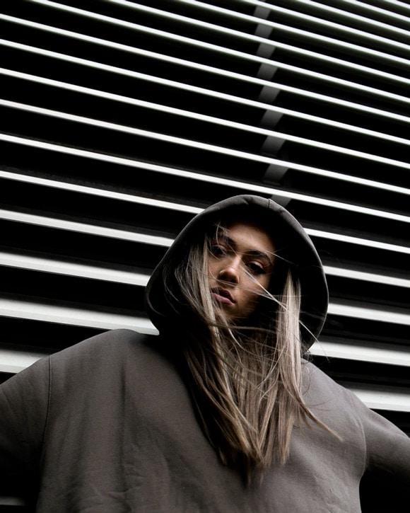 Girl in hoodie against repeating pattern backdrop