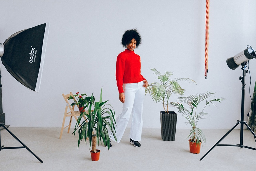 Woman posing in a studio with plants and lighting equipment